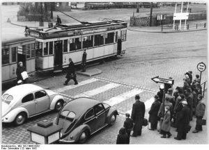 """Zentralbild-Schmidtke Me-Qu. 22.3.52. Erster Fussgängerschutzweg in Berlin. Die Berliner Verkehrspolizei hat in Niederschöneweide zur Sicherung des Fussgängerverkehrs eine Neuerung geschaffen. Über den Fahrdamm führt ein """"Fussgängerschutzweg"""", auf dem die Fussgänger das Vorrecht haben. Der Schutzweg ist kenntlich durch je zwei parallel laufende weisse Streifen quer zur Fahrbahn und durch rot-weisse Leuchtpfeile mit der Aufschrift """"Fussgänger"""". Die dort gesammelten Erfahrungen sollen richtungsgebend sein für die Errichtung weiterer derartiger Anlagen in anderen verkehrsreichen Strassen. UBz: Der erste Fussgängerschutzweg vor dem Ausgang des S-Bahnhofs Schönweide, vor dem sich leider bisher viele Verkehrsunfälle ereigneten."""